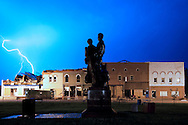 """Lightning flashes through the sky over downtown Elmwood, IL as Lorado Taft's """"The Pioneers"""" statue looks on. The buildings in the background were damaged in a tornado several weeks before."""