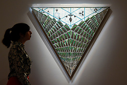 "© Licensed to London News Pictures. 21/04/2017. London, UK.  A staff member views ""Triangle of Hope"", 2008, by Monir Farmanfarmaian, (est. GBP 100-200k), at a preview at Sotheby's, New Bond Street, of upcoming sales of Arts of the Islamic World, 20th century Middle East Art and Orientalist art. Photo credit : Stephen Chung/LNP"