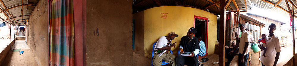 "The Double K in front of Kool King's house write some lyrics for their new album ""Problem"", while friends and neighbours gather to listen, Kroo Bay, Freetown, Sierra Leone."