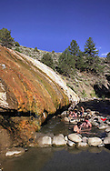 Buckeye Hot Springs - Two hot springs sources feeding two soaking pools adjacent to a clear stream on the eastern slope of the Sierras. The two main sources at Buckeye Hot Springs emerge from the side of the hill and cool rapidly at they flow downhill. One of the sources flows into a large pool that maintains a temperature of about 100 degrees F. The other source is larger and flows into the creek where it has been dammed up with rocks, forming several pools. Each of these pools differs slightly in temperature, ranging from 110 to 95 degrees F. The temperature will vary depending upon the amount of creek water flowing into the pools. The largest pool is under an overhang created by the hot springs water and offers a cave like setting.