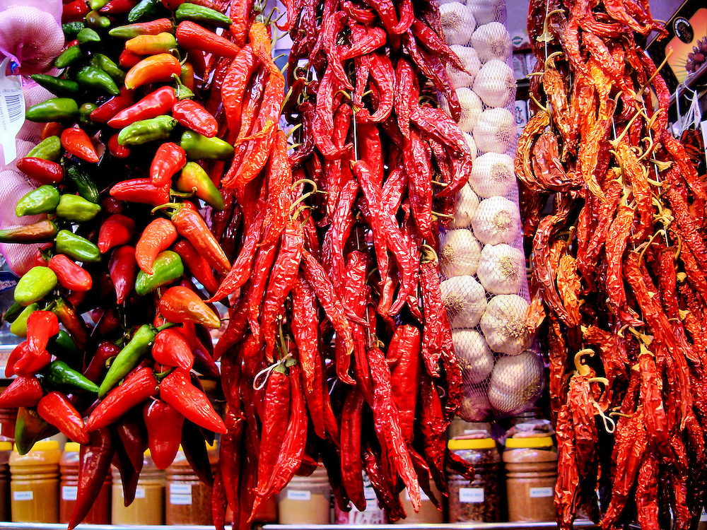 Colorful Chili Peppers and Garlic at La Boqueria Market in Barcelona, Spain<br /> This hanging display of chili peppers at La Boqueria Market in Barcelona, Spain, lets you decide how much you want to spice things up.  On a hotness scale of 1 to 5, the ones on the left &hellip; including the green Anaheim, the bright red Spanish Piquillo, the twisted green Spanish Guernica and the small green Pimiento de Padr&oacute;n from Northern Spain &hellip; are all rated a one.   The long red, dried ones are Cayenne and on the right are Aji Rojo, both rated a four or five.   And don&rsquo;t forget the garlic bulbs.