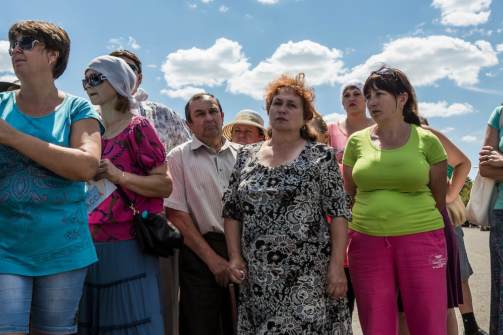 GRABOVO, UKRAINE - JULY 21: Local residents gather to watch as the bodies of victims of Malaysia Airlines flight MH17 are removed from the scene of the crash on July 21, 2014 in Grabovo, Ukraine. Malaysia Airlines flight MH17 was travelling from Amsterdam to Kuala Lumpur when it crashed killing all 298 on board including 80 children. The aircraft was allegedly shot down by a missile and investigations continue over the perpetrators of the attack. (Photo by Brendan Hoffman/Getty Images) *** Local Caption ***