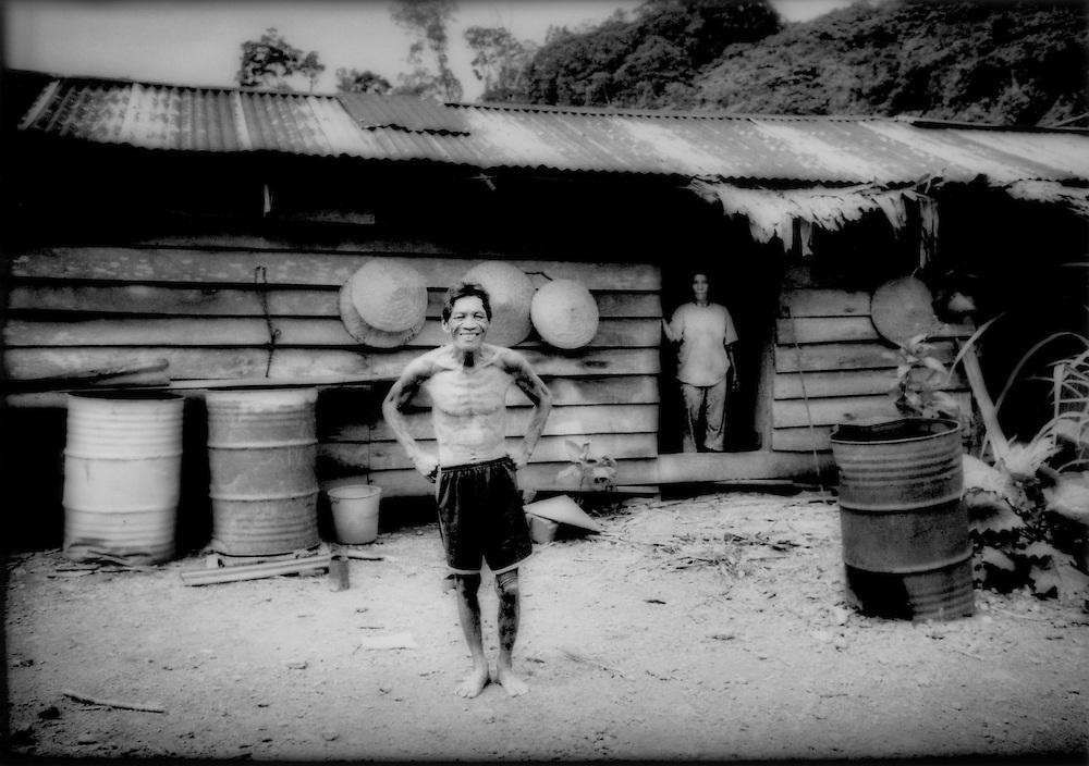 Headman of Rumah Lawan Longhouse at annex up above the main longhouse near the swiddle fields, deep interior of the Borneo rainforest, Sarawak, Malaysian Borneo.