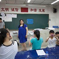BEIJING, JULY,12-14,2013 : Teilnehmer eines Foto Workshops in der CAOCHANGDI MITTELSCHULE fotografieren Lehrerin Wang.