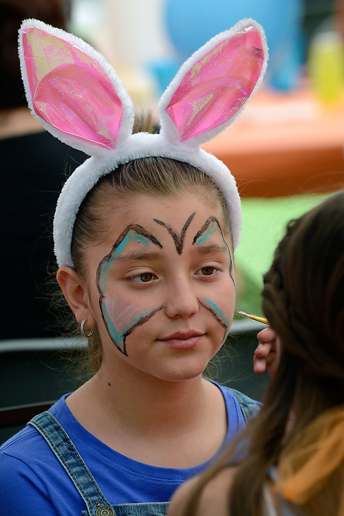 """jt041517c/a sec/jim thompson/ Nicole Proano-11 gets a butterfly face painting to go with her rabbit ears at the Victory Outreach Albuquerque Church's HOPE Easter Egg Hunt and care Basket Giveaway at Roosevelt Park. Which is part of the """"Operation Hope/I (heart) ABQ """" campaign.   Saturday April 15, 2017. (Jim Thompson/Albuquerque Journal)"""