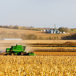 A John Deere combine stirs up dust on a dry day in western Iowa as it harvests a field of soy beans.