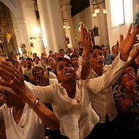 Women pray to Santa María la Antigua, the patron saint of Panama City, during a mass in the cathedral in the plaza of Panama City, Panama on Sunday, September 9, 2007. (Photo/Scott Dalton).