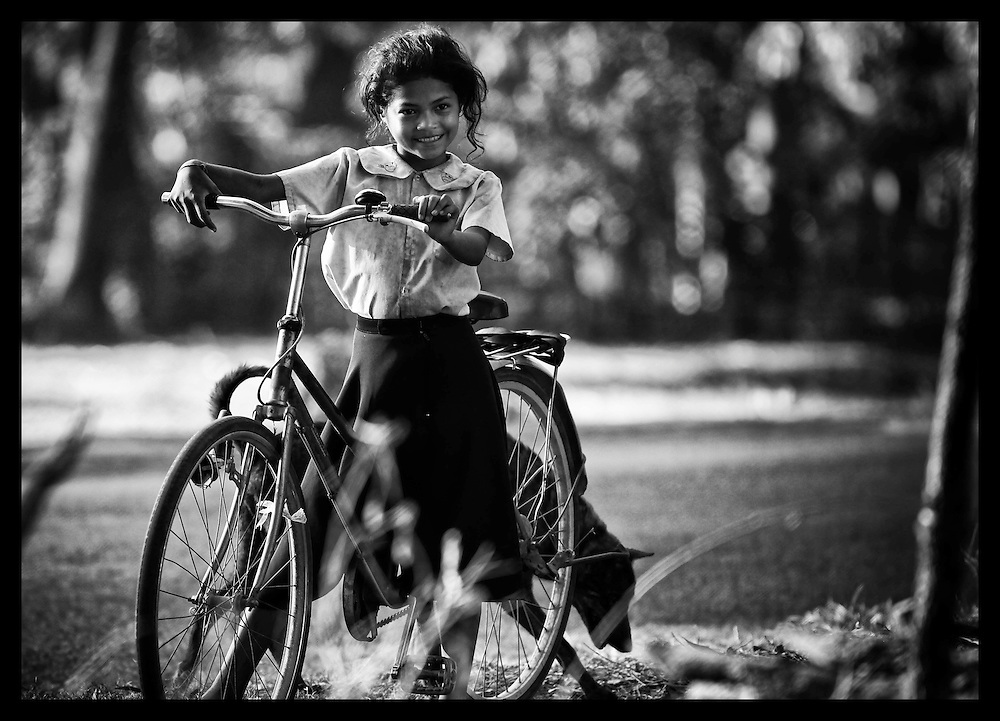 A young Cambodia girl stops her bicycle near the temples of Angkor Wat.  In 1998 most rural Cambodians traveled by bicycle.