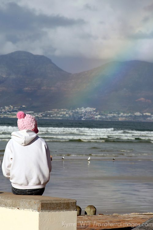 Africa, South Africa, Muizenberg.  Surfer watches waves and rainbow at Muizenberg Beach on the Cape peninsula, near Cape Town.