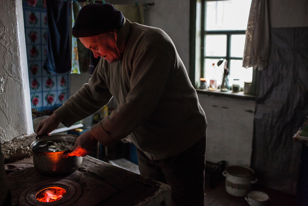 SNEZHNE, UKRAINE - JANUARY 25, 2015: Vladimir Moroz, who used to operate his own small coal mine across the street from his house, cooks soup over a coal-fired stove in his house in Snezhne, Ukraine. The area is well known for its many coal mines, both large operations and small backyard operations. CREDIT: Brendan Hoffman for The New York Times