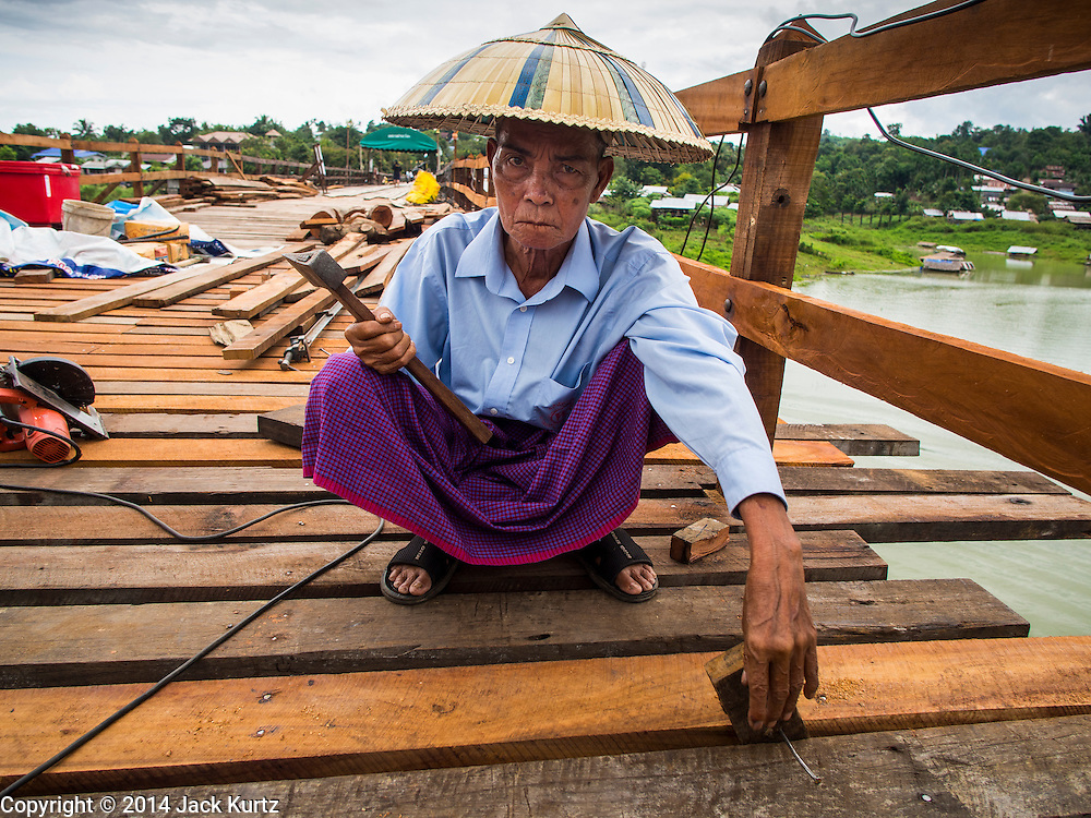 16 SEPTEMBER 2014 - SANGKHLA BURI, KANCHANABURI, THAILAND: A member of the Mon community working on the repair of the Mon Bridge. The 2800 foot long (850 meters) Saphan Mon (Mon Bridge) spans the Song Kalia River. It is reportedly second longest wooden bridge in the world. The bridge was severely damaged during heavy rainfall in July 2013 when its 230 foot middle section  (70 meters) collapsed during flooding. Officially known as Uttamanusorn Bridge, the bridge has been used by people in Sangkhla Buri (also known as Sangkhlaburi) for 20 years. The bridge was was conceived by Luang Pho Uttama, the late abbot of of Wat Wang Wiwekaram, and was built by hand by Mon refugees from Myanmar (then Burma). The wooden bridge is one of the leading tourist attractions in Kanchanaburi province. The loss of the bridge has hurt the economy of the Mon community opposite Sangkhla Buri. The repair has taken far longer than expected. Thai Prime Minister General Prayuth Chan-ocha ordered an engineer unit of the Royal Thai Army to help the local Mon population repair the bridge. Local people said they hope the bridge is repaired by the end November, which is when the tourist season starts.    PHOTO BY JACK KURTZ