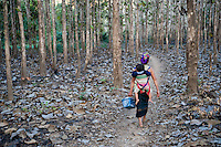 A woman walks with her child strapped to her back through the woods near her village, near Luang Prabang, Laos