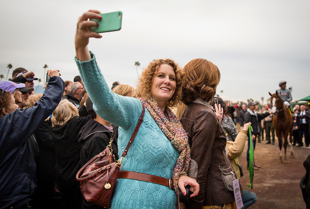 January 09, 2016: A woman takes a selfie in the winners circle with California Chrome and Victor Espinoza in the distance, at Santa Anita Park, Arcadia CA. Evers/ESW/CSM