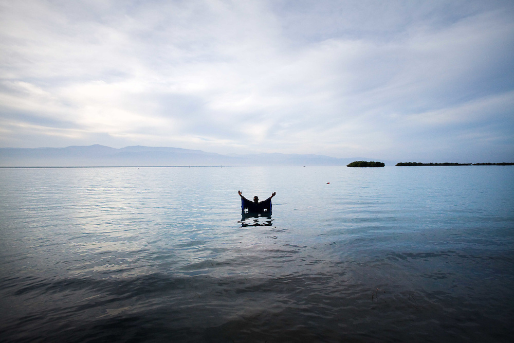 """Reverend Pierre Altés prays in the ocean after baptising several congregants. Altés, from Port Au Prince,  says """"I just come here to baptize people. For a long time Titanyen was known to be a place where corpes were dumped, but now there are more police watching the road so that is not happening. But it is still an area where you want to be careful."""""""