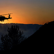 A water helicopter circles above the remaining fire looking for a spot to drop as firefighter await further instructions on the buff north of the University of Portland.