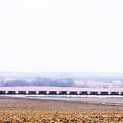 Rolling south across the prairies near the conveniently named Prairie City, IL, BNSF train U-KEEMAD speeds its load of iron ore from the Missabe Range in Minnesota to the steel mills of Madison, IL, near St. Louis.