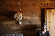 Juana Devalan Pixcar sits on a bench in the kitchen of her adobe home.  Portrero Viejo, Guatemala.