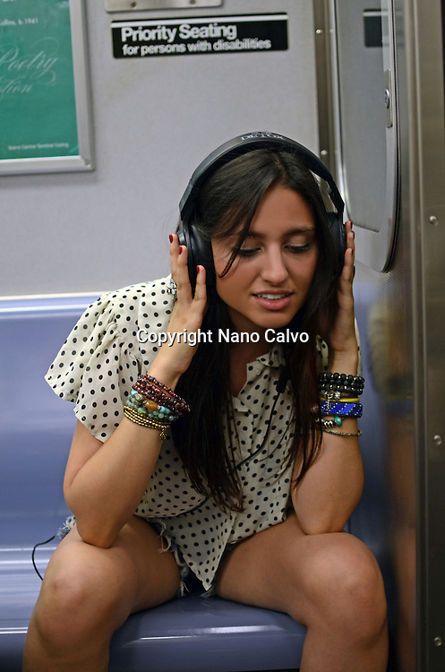 Attractive young mixed race woman listening to music in subway train, New York City