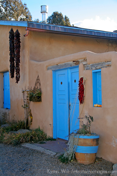 USA, New Mexico, Santa Fe. Typical adobe style home with painted wood door and dried chilis.