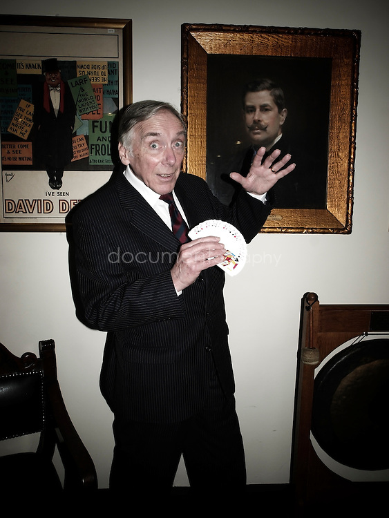 Jack Delvin, the current and 13th President of The Magic Circle, in front of a portrait of David Devant, the first President.