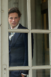 handsome man in a suit looking through a window