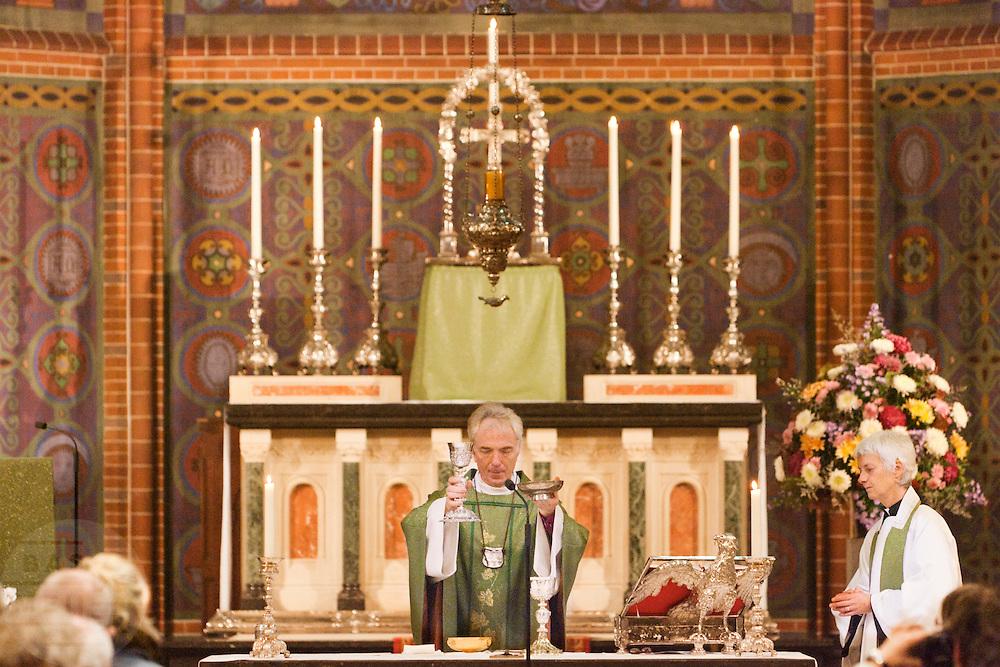 Aartsbisschop Joris Vercammen treft de voorbereidingen voor de communie. Op zondag 31 oktober is in de Getrudiskathedraal in Utrecht  Annemieke Duurkoop als eerste vrouwelijke plebaan van Nederland ge&iuml;nstalleerd. Duurkoop wordt de nieuwe pastoor van de Utrechtse parochie van de Oud-Katholieke Kerk (OKK), deze kerk heeft geen band met het Vaticaan. Een plebaan is een pastoor van een kathedrale kerk, die eindverantwoordelijk is voor een parochie. Eerder waren bij de OKK al twee vrouwelijk priesters ge&iuml;nstalleerd, maar die zijn geen plebaan.<br /> <br /> Archbishop Joris Vercammen is preparing the sacraments. At the St Getrudiscathedral in Utrecht the first female dean of the Old-Catholic Church (OKK), Annemieke Duurkoop, is installed together with a new pastor Bernd Wallet. The church has no connections with the Vatican.