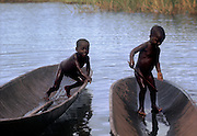 Boys of Libinza tribe playing in canoes. The Libinza live on the islands of the Ngiri River, tributary of the Ubangi River, Democratic Republic of the Congo, Africa.