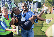 EAST LONDON, SOUTH AFRICA - FEBRUARY 20: Patience Khumalo of Athletics Gauteng North (AGN) is helped after winning the women's race during the ASA Marathon Championships in East London on February 20, 2015 in South Africa. (Photo by Roger Sedres/Gallo Images)