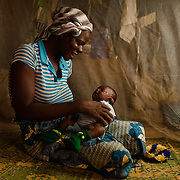 Fatbinta Sawadogo (30) and her daughter, Alima Ouedraogo (1 month), under their mosquito net in the village of Songodin in the Sanmatenga region of Burkina Faso on 25 February 2014. Mosquito nets greatly decrease the incidence of malaria by reducing the risk of being bitten by the nocturnal Anopheles mosquito, which carries the malaria parasite.
