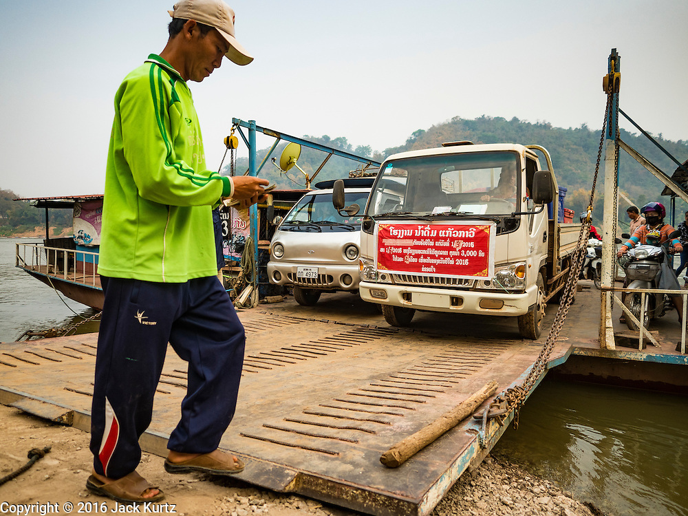 11 MARCH 2016 - LUANG PRABANG, LAOS: A crewman guides cars off a ferry across the Mekong River near Luang Prabang. Laos is one of the poorest countries in Southeast Asia. Tourism and hydroelectric dams along the rivers that run through the country are driving the legal economy.       PHOTO BY JACK KURTZ