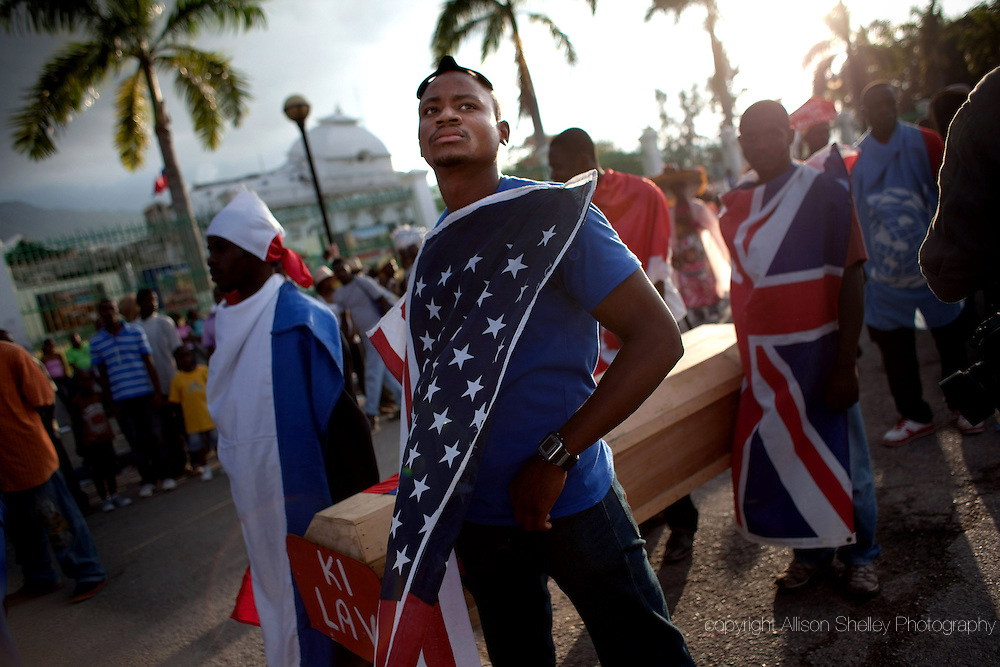 """Men wearing flags representing the UN and countries with past and present interests in Haiti, carry a coffin draped in a Haitian flag with a placard reading """"what life"""" march past the earthquake-destroyed Haitian national palace on the first day of the Port-au-Prince carnival celebration, March 6, 2011 in Port-au-Prince, Haiti-- over a year after the earthquake.  Last year's celebration was cancelled."""