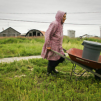 Vera Spein carries river water back to her home to be used in washing clothes in the village of Kwethluk