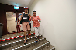 Aishah is helped by her older son Jafni down the stairs after practices at an air rifle range in Singapore, 11 June 2014. While the road to recovery and shooting has been slow and painful, the determined and cheerful mother-of-two grown sons took it all in her stride. She divides her time between exercising and training at an air rifle club while giving motivational talks to share her extraordinary life which has inspired many.