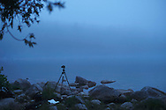 A tripod and camera on the rocky beach at Jordan Pond in Acadia National Park, Maine.