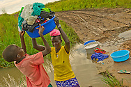 In the Nimule Payan area of Sudan, Rebecca Akoul does her family laundry in a creek by the side of a dirt road.