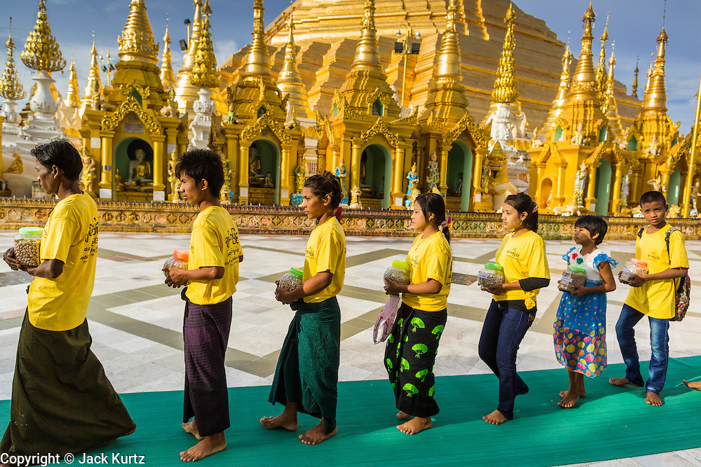 07 JUNE 2014 - YANGON, YANGON REGION, MYANMAR: Children participate in a small private procession during a merit making ceremony for their parents' company at Shwedagon Pagoda in Yangon. Shwedagon Pagoda is officially called Shwedagon Zedi Daw and is also known as the Great Dagon Pagoda and the Golden Pagoda. It's a 99 metres (325 ft) gilded pagoda and stupa located in Yangon. It is the most sacred Buddhist pagoda in Myanmar with relics of the past four Buddhas enshrined within: the staff of Kakusandha, the water filter of Koṇāgamana, a piece of the robe of Kassapa and eight strands of hair from Gautama, the historical Buddha.   PHOTO BY JACK KURTZ