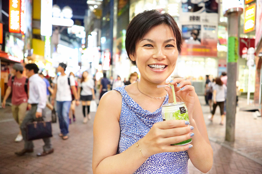 Lifestyle image of smiling Japanese woman with canned drink in Shibuya Tokyo during Summer night