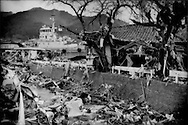 A tug boat has been deposited high above the harbor, which is more than 1 kilometer away, by a massive tsunami above a clogged waterway behind a house that may not have originally stood in that locations and the branches of the cherry trees are strewn with clothing and refuse at a second storey level.  Ofunato, Iwate Prefecture, Japan.