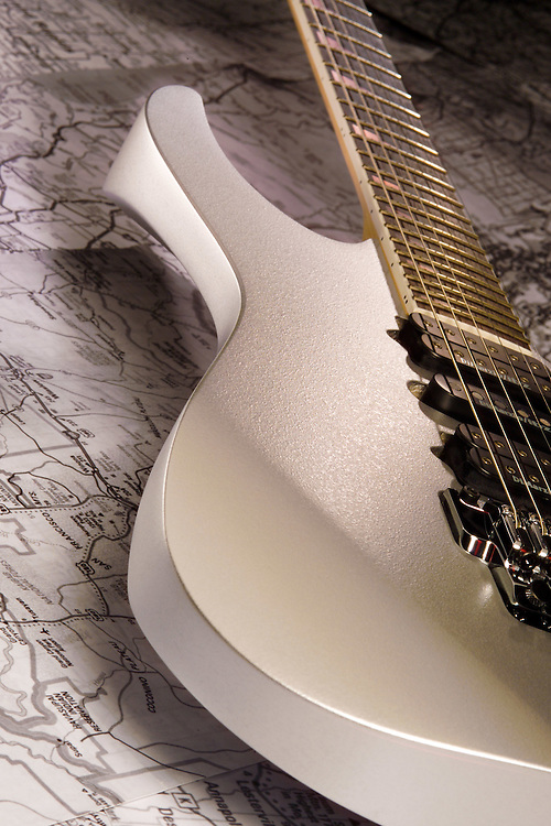 White Ibanez electric guitar hovering over black and white road map.