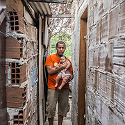 Paulo (49), Maria (20) and their daughter with microcephaly Eduarda Vitoria (5 months), in front of their house, a shelter inside the slum of Santa Luzia in Recife, Pernambuco. Both of them are unemployed and extremely poor