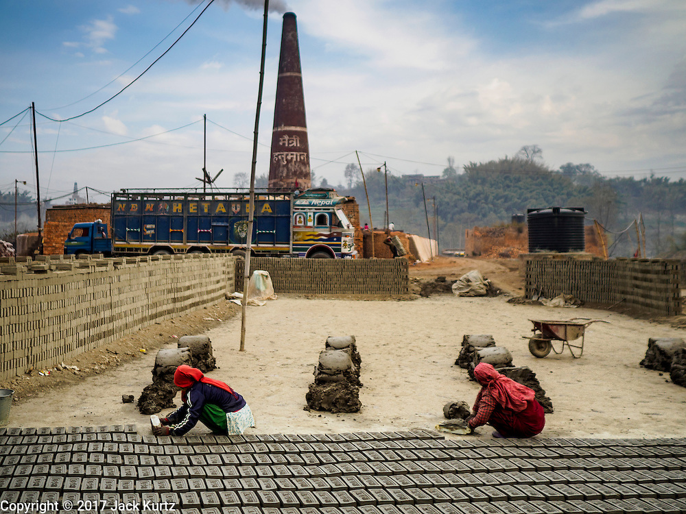 03 MARCH 2017 - BAGMATI, NEPAL: Workers use molds to form bricks from clay at a brick factory in Bagmati, near Bhaktapur. The bricks will lay out for one or two days and then taken to the kiln (the smokestack in the background) for baking. There are almost 50 brick factories in the valley near Bagmati. The brick makers are very busy making bricks for the reconstruction of Kathmandu, Bhaktapur and other cities in the Kathmandu valley that were badly damaged by the 2015 Nepal Earthquake. The brick factories have been in the Bagmati area for centuries because the local clay is a popular raw material for the bricks. Most of the workers in the brick factories are migrant workers from southern Nepal.       PHOTO BY JACK KURTZ