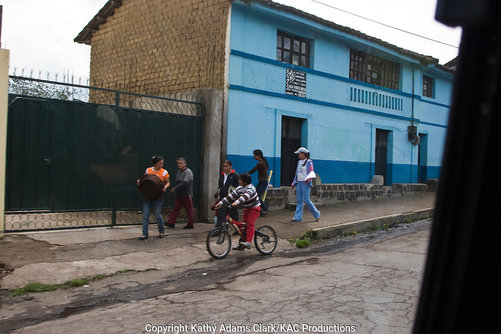 child on a bike, talking with lady with laundry basket, along the Street in rural Ecuador.