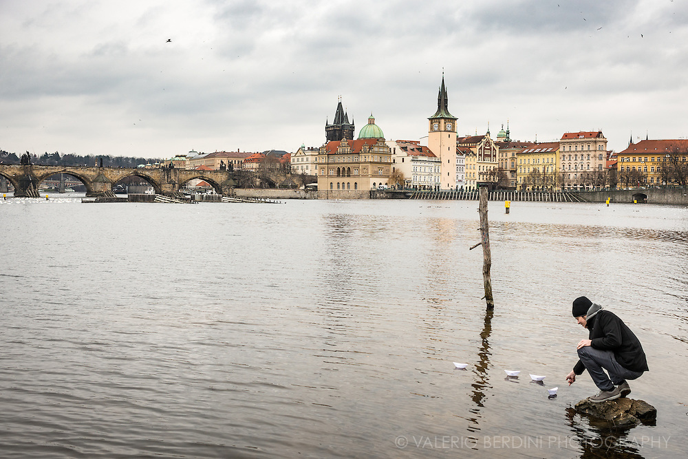 A man send wishful messages written on paper boats left floating in the Vltava River in Prague.