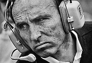 This 1980 portrait of team owner Frank Williams says perhaps more about his dogged determination and business acumen than his resume. Williams had just won his first  Constructor's Championships and the first of seven World Driver's Championships, but his grim no-nonsense visage made it clear he was just starting. Williams would win eight more Constructor's titles between 1982 and 1997. <br /> <br /> He entered Formula One in 1967, running Piers Courage. By 1977, he had formed Williams Grand Prix Engineering with design engineer Patrick Head, then acquired Saudia Airlines sponsorship in 1978, and used these elements to build the FW08 that brought Alan Jones his World Championship. From that moment forward, Williams F1 would become a force in Formula One for the next 33 years. <br /> <br /> Despite becoming paralyzed in 1986 following a road accident, Williams never lost his drive to succeed or his gift for employing the most talented. Including Australia's Alan Jones, Finland's Keke Rosberg, Britain's Nigel Mansell,and Damon Hill, France's Alain Prost, Brazil's Nelson Piquet, and Canada's Jacques Villeneuve, each captured one Drivers' title with the team. <br /> <br /> Williams was awarded a CBE for his services to motor racing in 1987 and was knighted in January 1999.