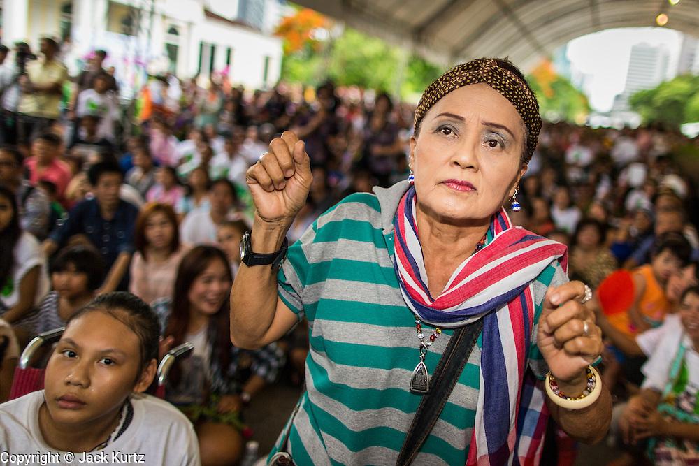 """15 JUNE 2014 - BANGKOK, THAILAND: A woman dances while a police band performs in Lumpini Park in Bangkok. The Thai military junta, formally called the National Council for Peace and Order (NCPO), is sponsoring a series of events throughout Thailand to restore """"Happiness to Thais."""" The events feature live music, dancing girls, military and police choirs, health screenings and free food.   PHOTO BY JACK KURTZ"""