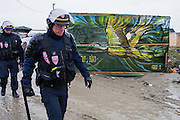 French police patrol the camp after a night of clashes between police and refugees.