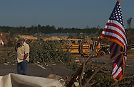 Rainsville, Alabama: A man talks to his insurance company as he walks across a shopping center parking lot on Friday. The school bus and landed from a school parking lot across the street. (PHOTO: MIGUEL JUAREZ LUGO)
