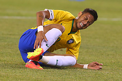 Sep 9, 2014; East Rutherford, NJ, USA; Brazil forward Neymar (10) grabs his ankle after being tripped up during the first half at MetLife Stadium.