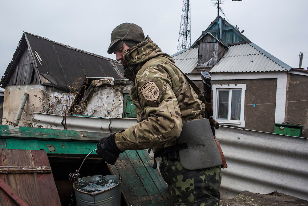 PERVOMAISKE, UKRAINE - NOVEMBER 18, 2014: Grigoriy Matyash, a member of the 5th platoon of the Dnipro-1 brigade, a pro-Ukraine militia, draws drinking water from a well behind a house near their post in Pervomaiske, Ukraine. CREDIT: Brendan Hoffman for The New York Times