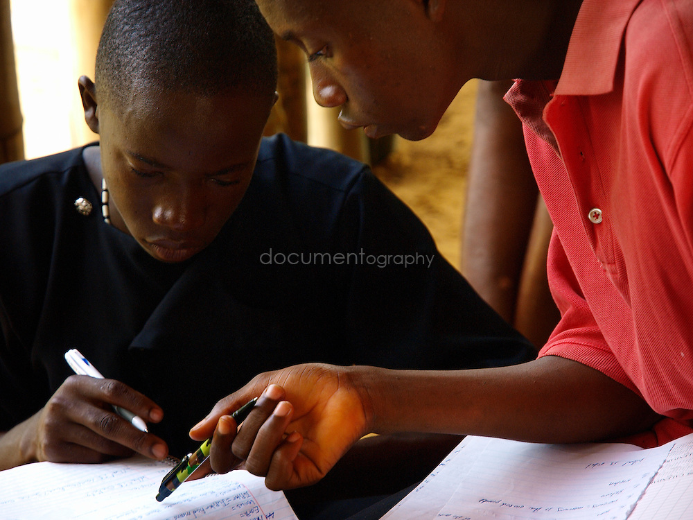 Pupils help each other study at J.S. Varfley School, Kingsville #7, Liberia.
